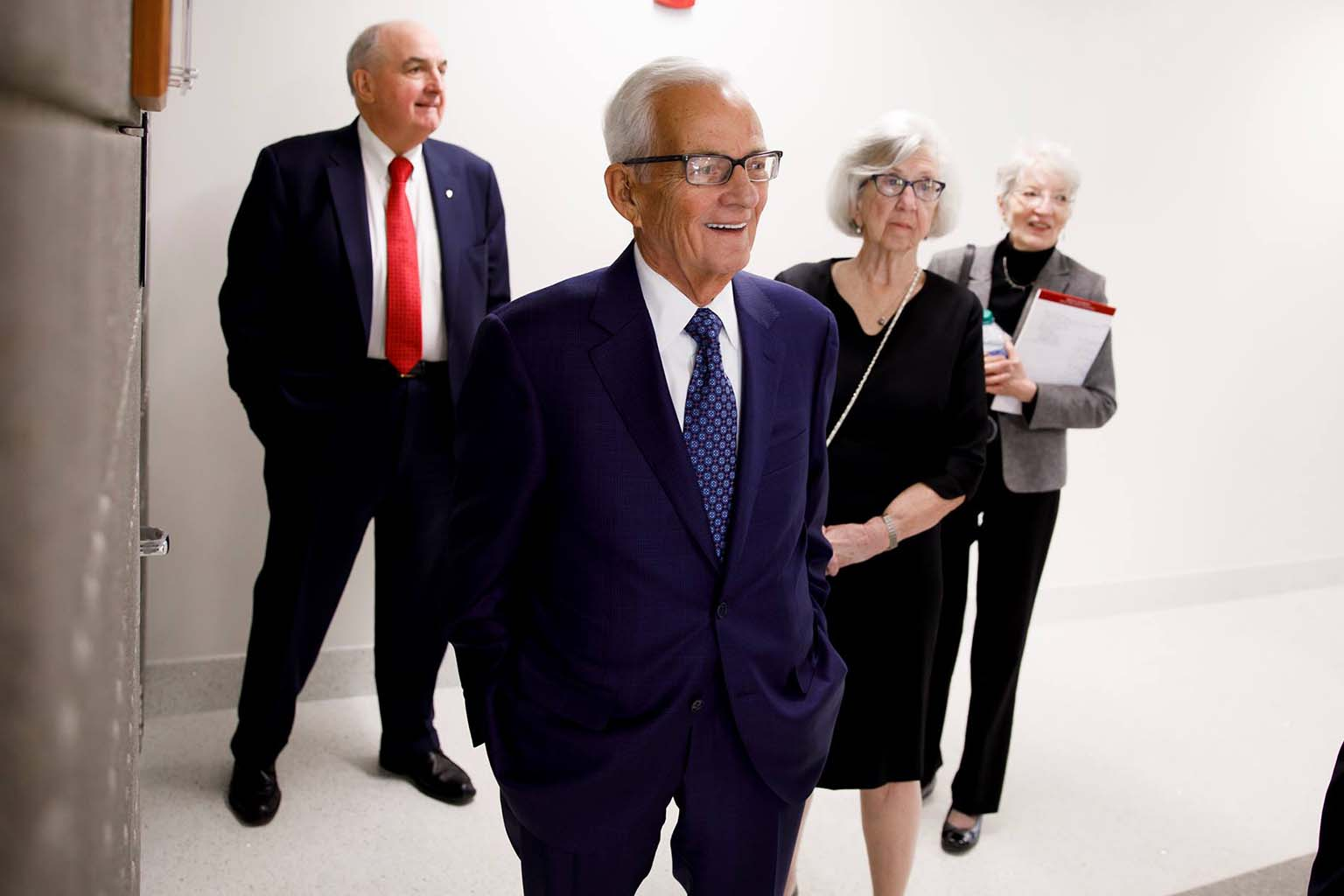 Paul O'Neill walks in the O'Neill Graduate Center with his wife, Nancy, and President Michael A. McRobbie and Prof. Kirsten Gronbjerg.