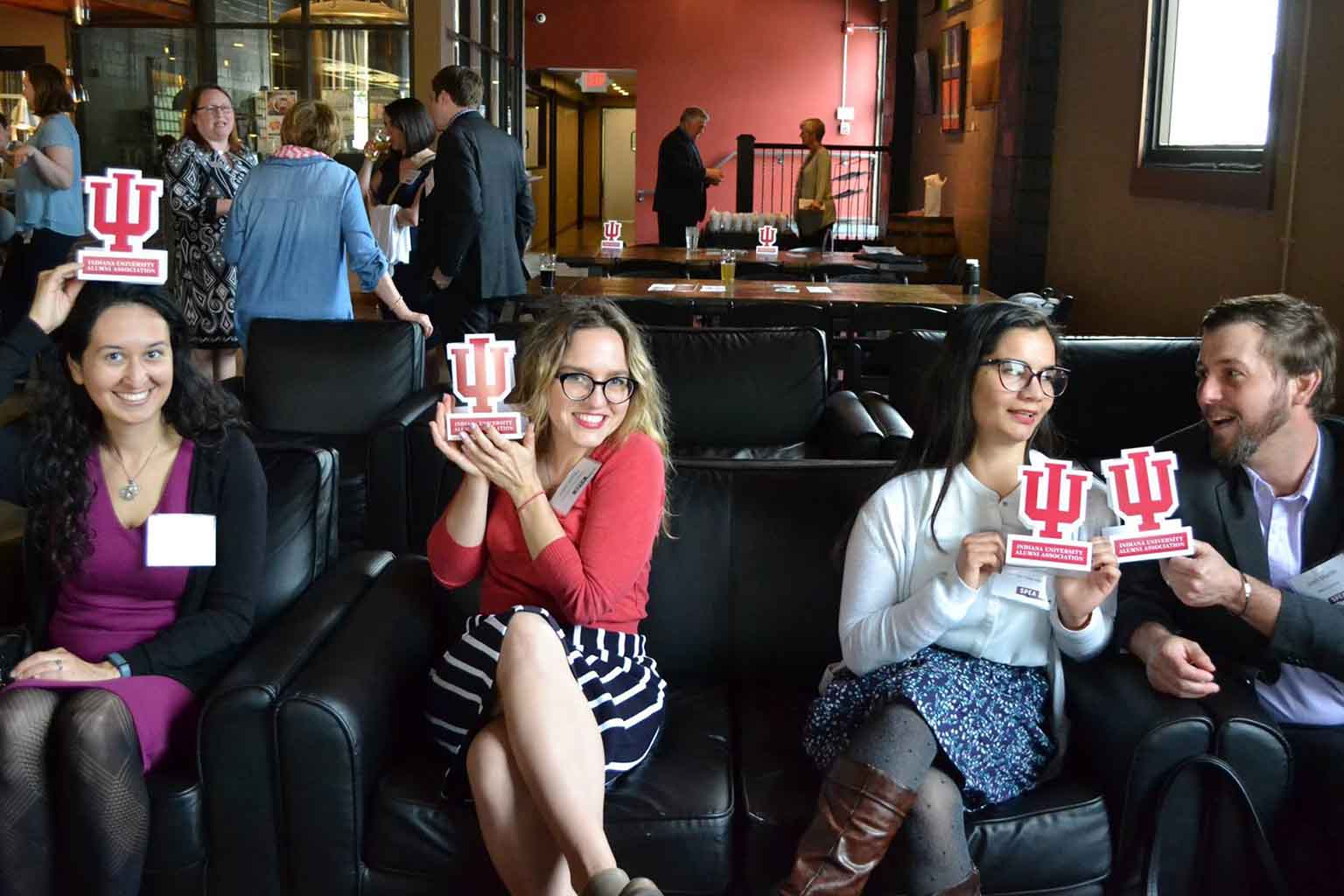 People pose with IU table tents in a bar or lounge.