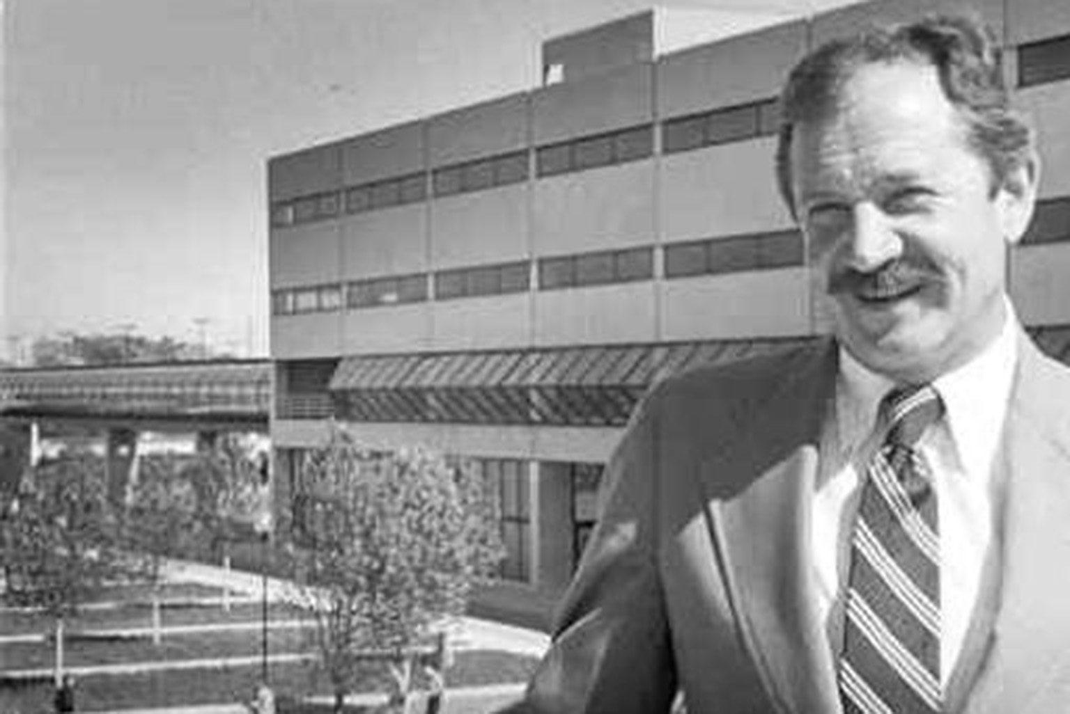Founding Dean Charles Bonser stands in front of a concrete building at IUPUI