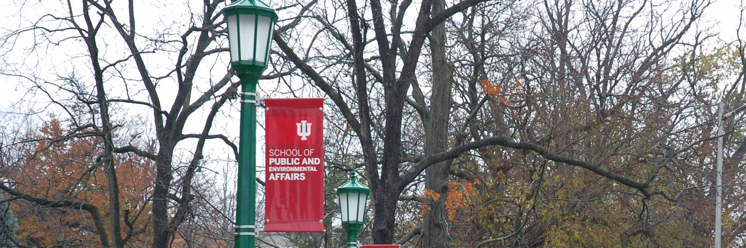 A red banner with the school's name hangs on a green lampost