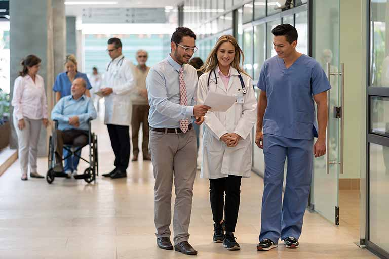 Man and woman chat in hospital hall