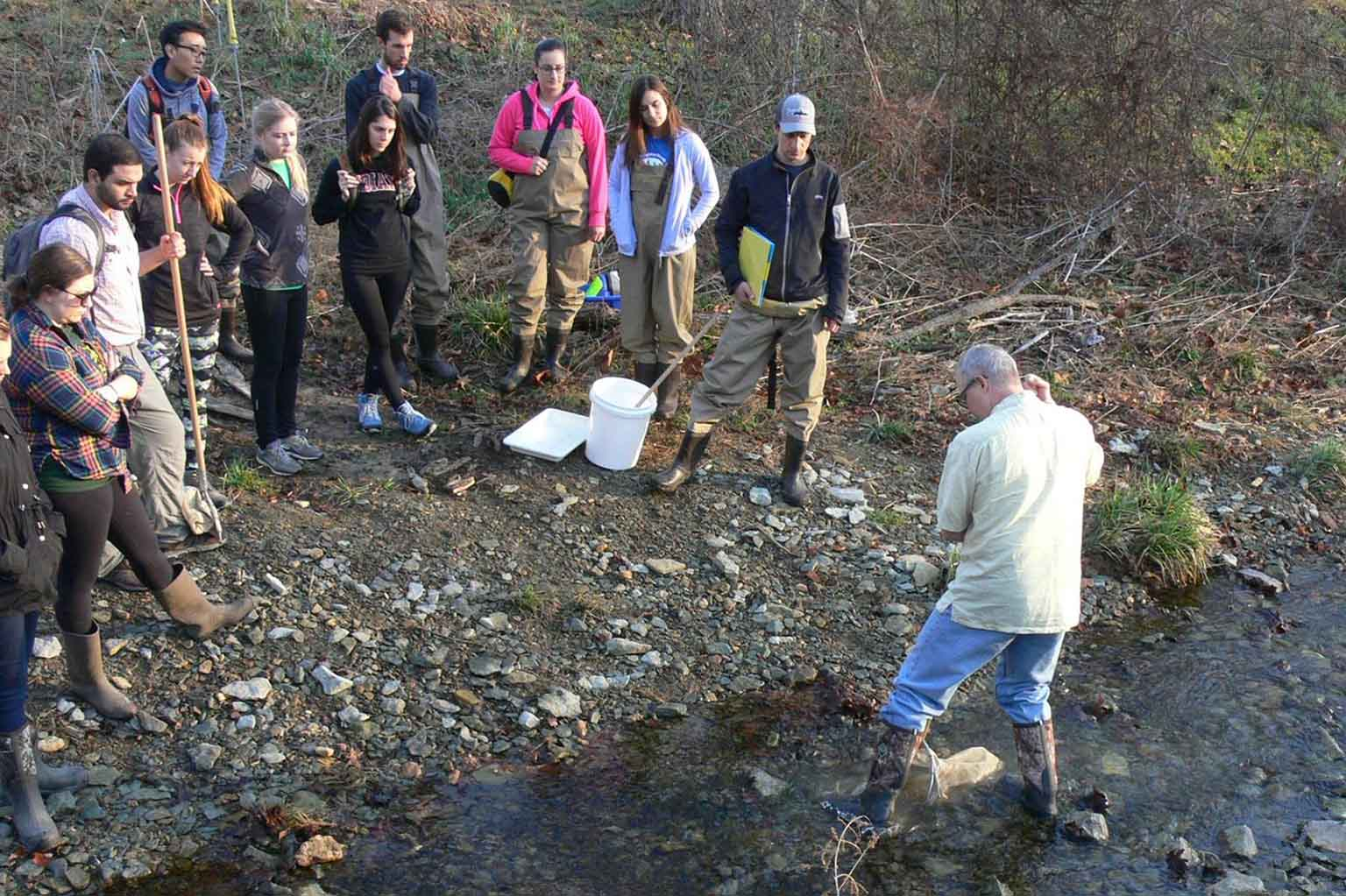 Circle of students watch a professor in a creek
