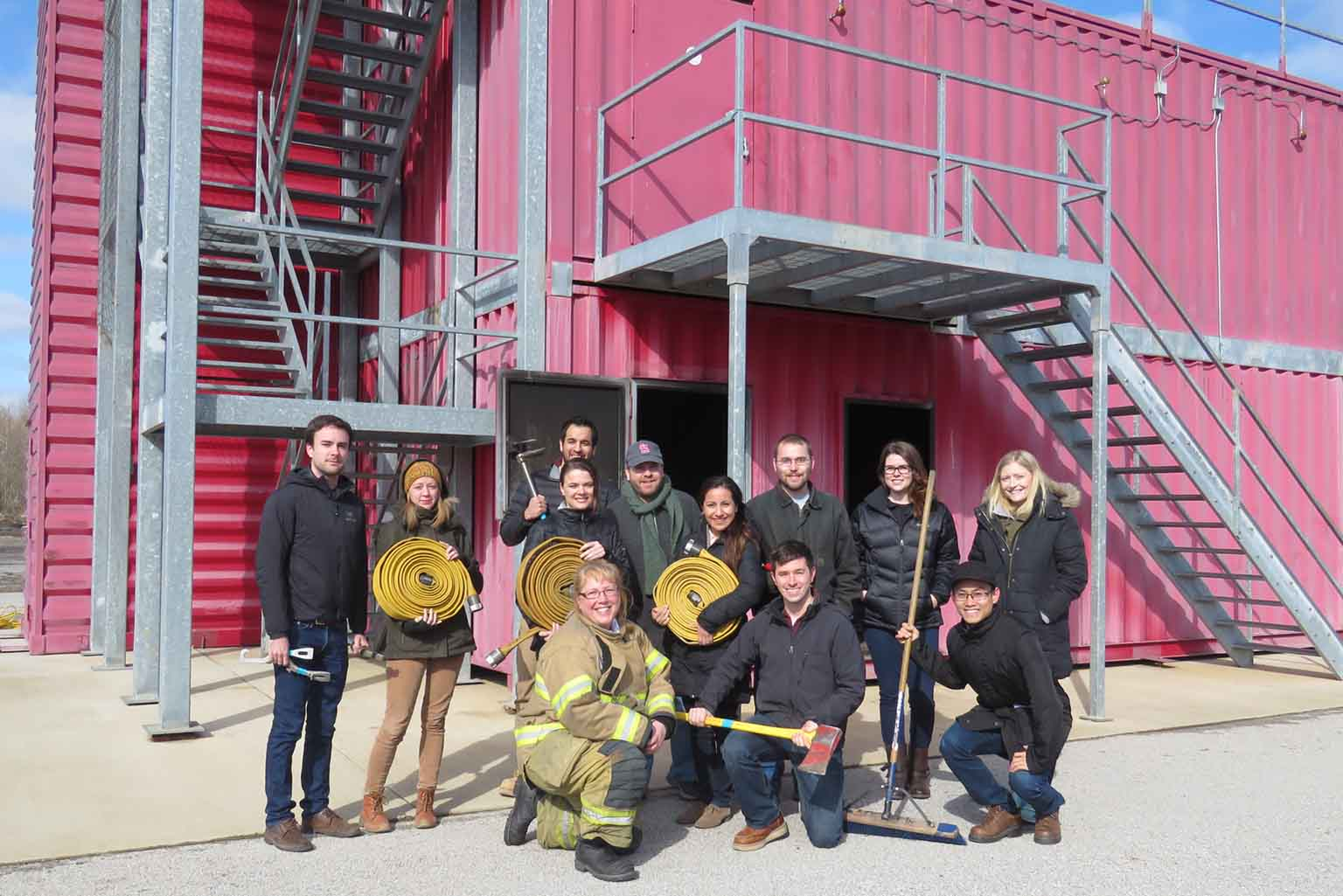 Students pose with fire equipment at the Bloomington Public Safety Training Center