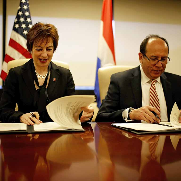 Dean Sian Mooney signs an agreement with Manuel Maria Caceres, the Paraguayan ambassador to the United States.