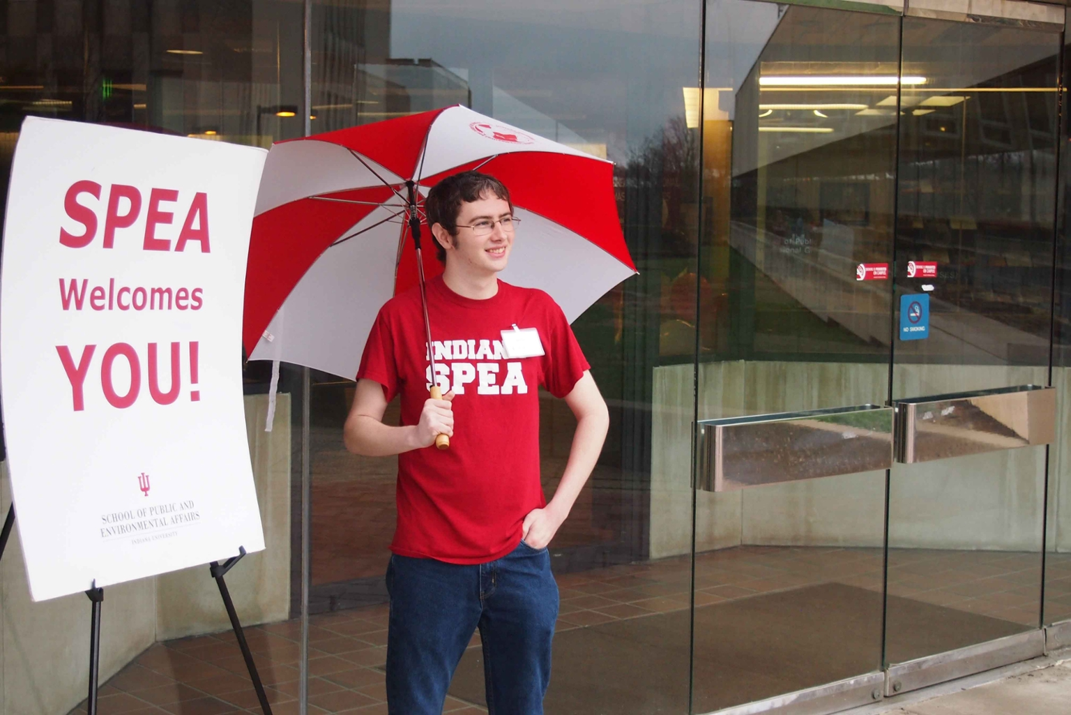 A student holds an umbrella by a welcome to SPEA sign.