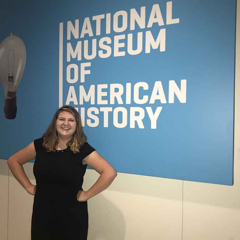 Student stands in front of sign reading National Museum of American History.